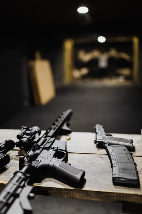 Black Assault Rifle on Black and Brown Wooden Table
