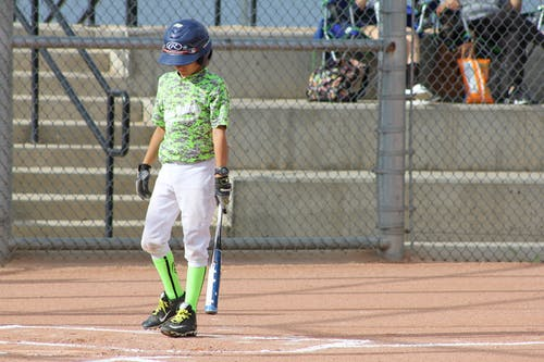Boy in Green T-shirt and White Pants Holding Black and Yellow Baseball Bat