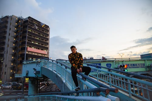 Stylish ethnic man sitting on railing of footbridge