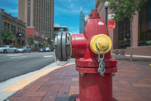 Empty paved sidewalk with red metal fire hydrant at roadside against blue sky in modern city