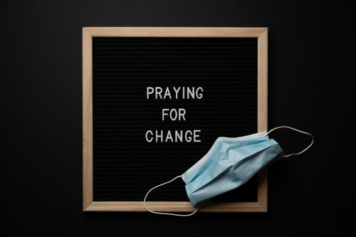 Praying for change text in frame near mask placed on blackboard