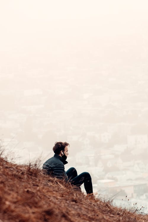 Lonely man sitting on hill and looking at cityscape