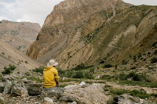 Back view of unrecognizable traveler in hat and yellow hoodie relaxing on stone and admiring picturesque landscape of mountainous valley against cloudy sky