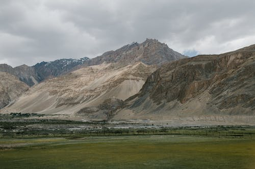Picturesque scenery of empty grassy meadow located near rocky mountain ridge against cloudy sky in Hunza Valley