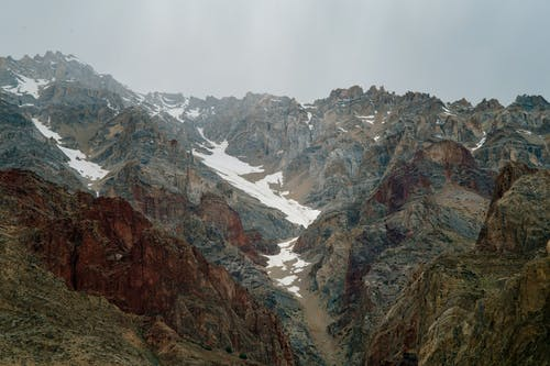 Spectacular landscape of massive rough rocky mountains with snowy slopes against overcast sky