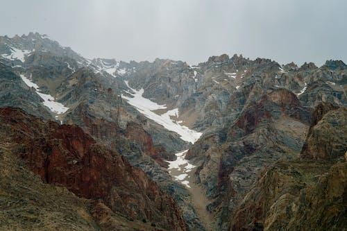 Rough rocky mountain ridge under cloudy gray sky