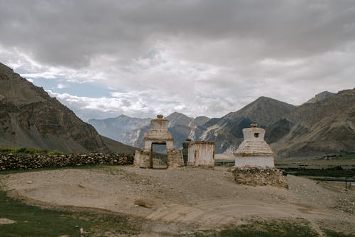 Old Buddhist chorten surrounded by rocky mountains against cloudy sky
