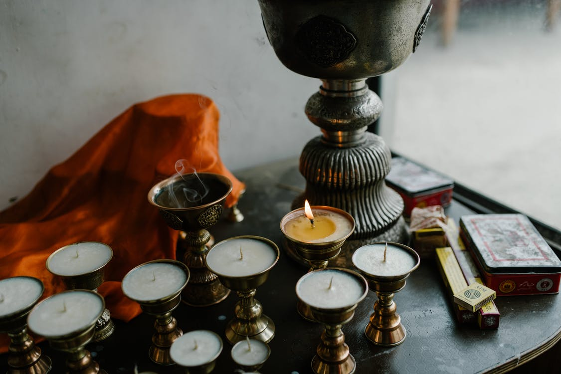 From above of small candles in copper butter lamps placed on table during traditional Tibetan ceremony in room