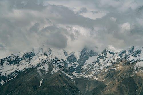 Snowy mountain peaks hidden under cloudy sky
