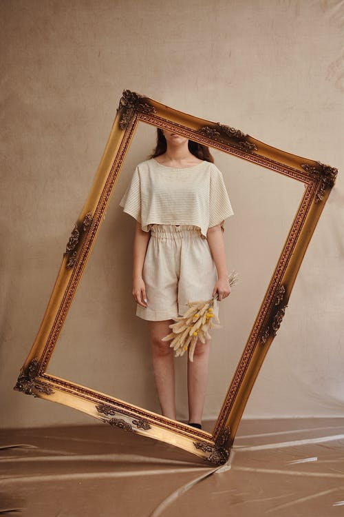 Crop anonymous female in trendy clothes standing with dry plant bouquet behind ornamental frame near wall