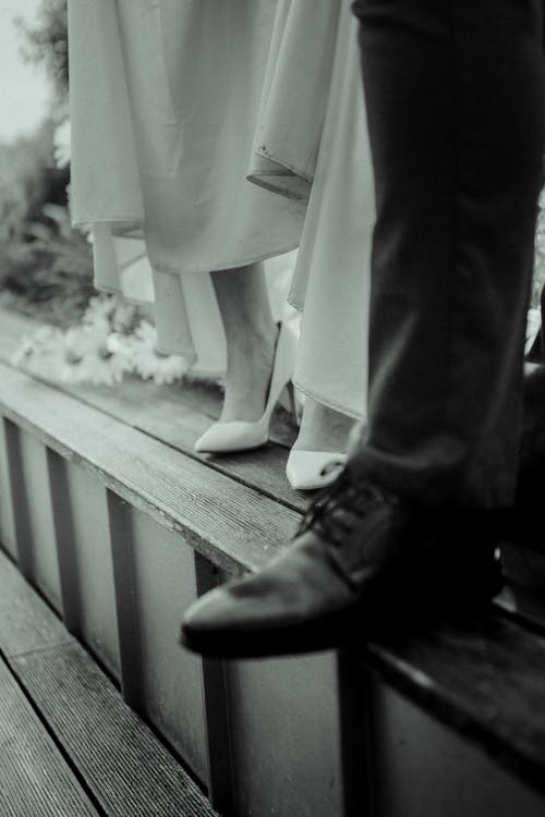 Grayscale Photo of Bride and Groom on Steps