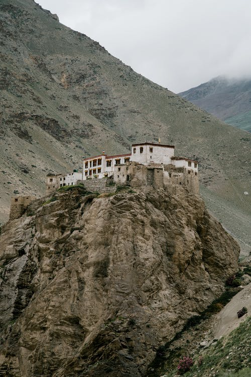 Old Buddhist monastery located on mountain peak in valley against misty sky