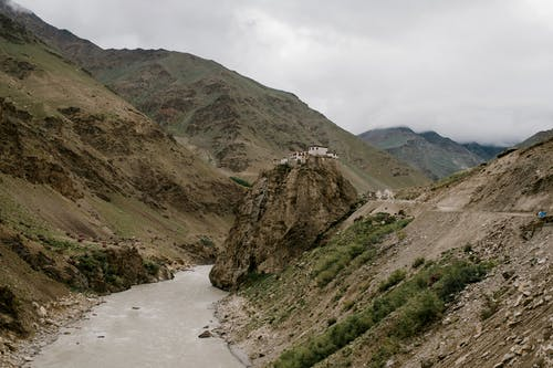 River flowing through mountainous valley near ancient Buddhist temple located on cliff peak