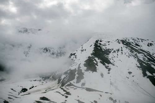 Picturesque snowy mountain valley under foggy sky
