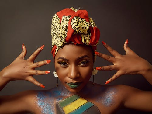 Stylish black woman in head wear with makeup demonstrating manicure