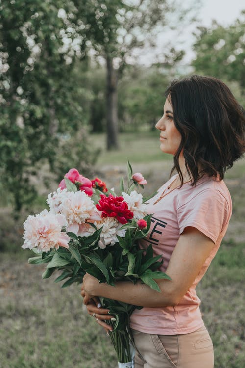 Attractive woman with flowers in park