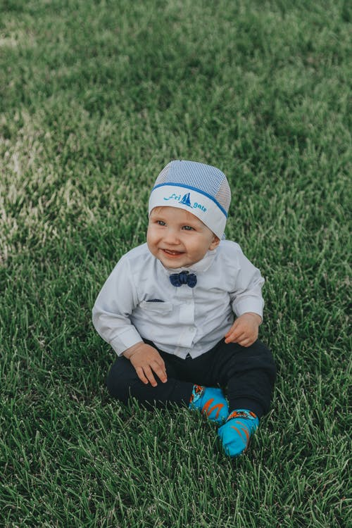 Full body of adorable child in formal wear and hat smiling and sitting on green grassy meadow at daylight
