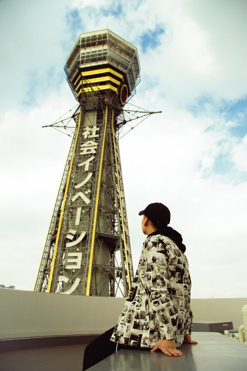 Young man admiring high tower while sitting on bench