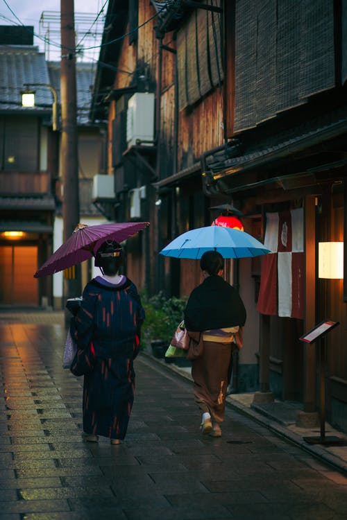 Woman in traditional outfits and umbrellas walking together