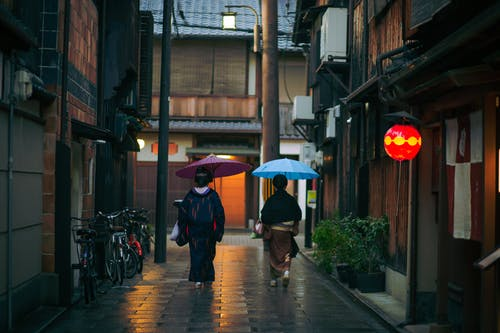 Asian woman in traditional clothes with umbrellas walking in alley