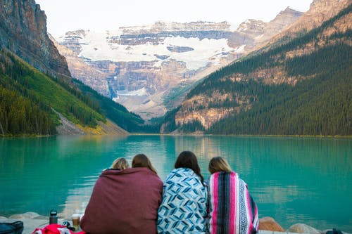 Back view of anonymous female travelers wrapped in warm blankets enjoying picturesque view of azure lake in highland