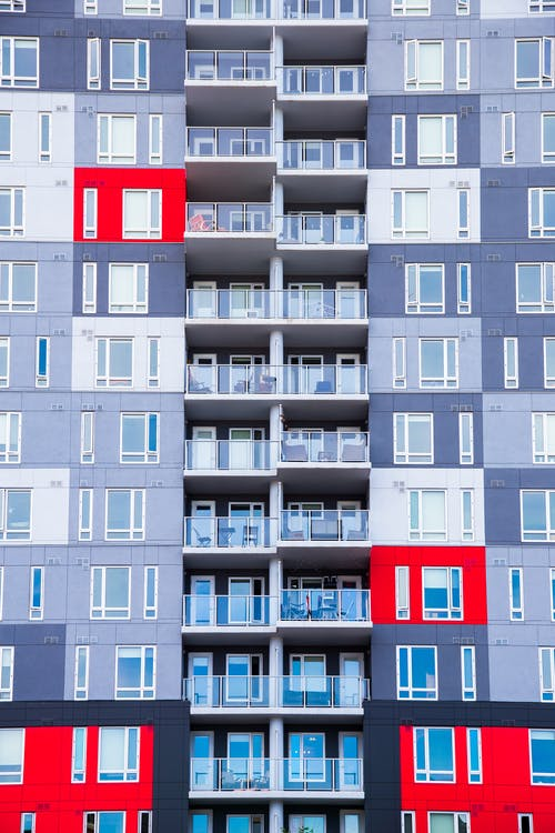 Facade of high rise residential building with colorful walls located in city in daytime