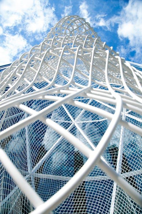 Modern construction against cloudy blue sky