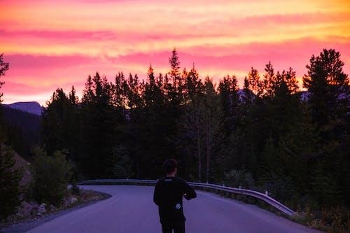 Man walking on asphalt road at colorful sunset