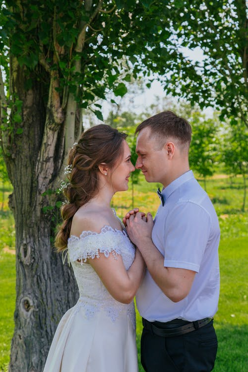 Happy newlywed couple standing in park