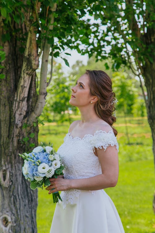 Side view of young bride in elegant dress holding bouquet of flowers and standing in garden while looking up