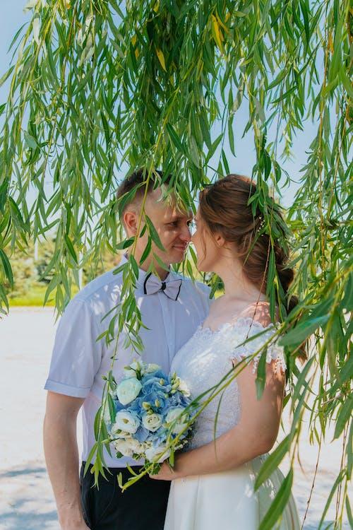 Happy couple standing under tree on wedding day