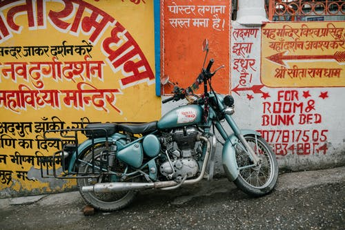 Old rusty motorcycle parked near shabby wall with various graffiti and inscriptions on city street