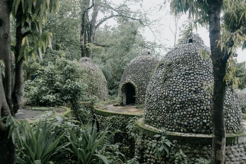 Exterior of aged stone meditation caves located on territory of Beatles Ashram in lush green tropical garden in India