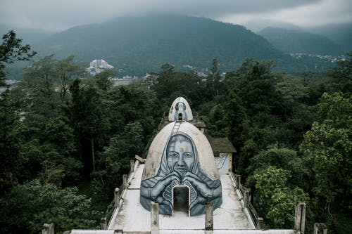 From above small domed caves with graffiti on Buddhist meditation house rooftop located in Beatles Ashram in lush green rainforest against cloudy sky in India