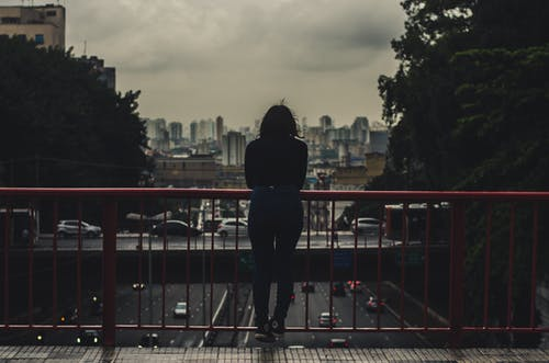 Woman in Black Jacket Standing on Red Metal Railings