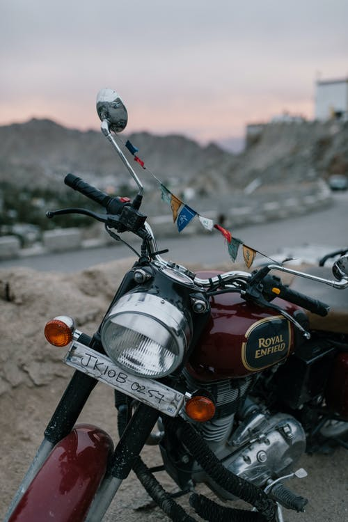 Retro motorcycle parked on dusty rural road in mountainous valley against sunset sky