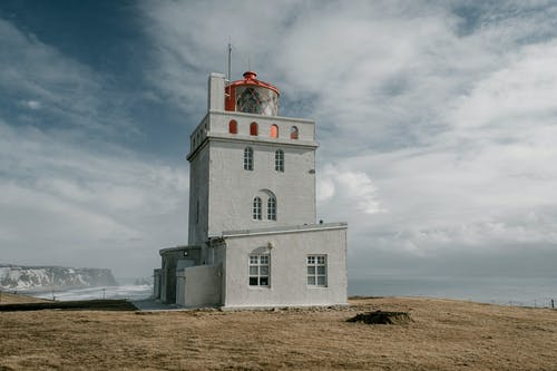 White lighthouse tower in front of waving sea against cloudy sky