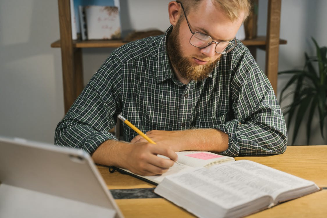 Man in Black and White Plaid Dress Shirt Writing on White Paper