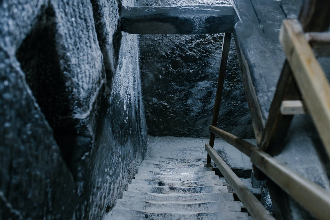 From above of aged stone stairway covered with salt in ancient cave with shabby walls and wooden railings in Registry Chamber of Salina Turda mine