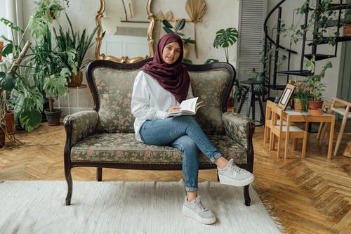 Woman in White Long Sleeve Shirt and Blue Denim Jeans Sitting on Gray Sofa Chair