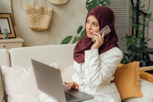Woman in a Hijab Using a Laptop and a Smartphone