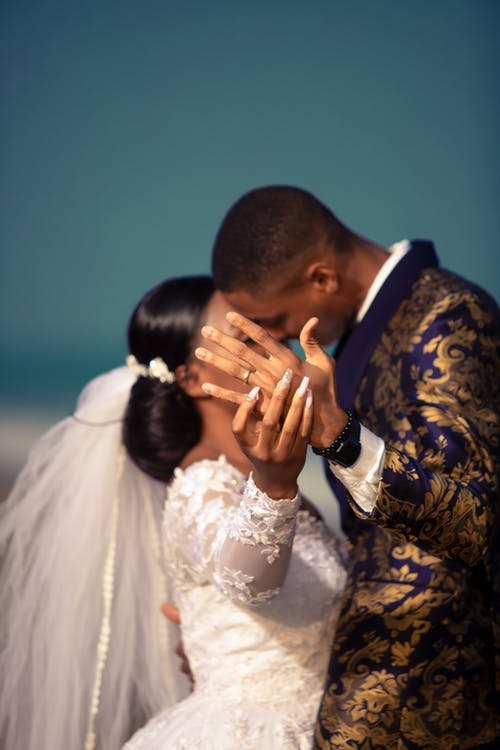 Side view of loving newlywed African American couple kissing gently and demonstrating ring on finger of groom at wedding ceremony