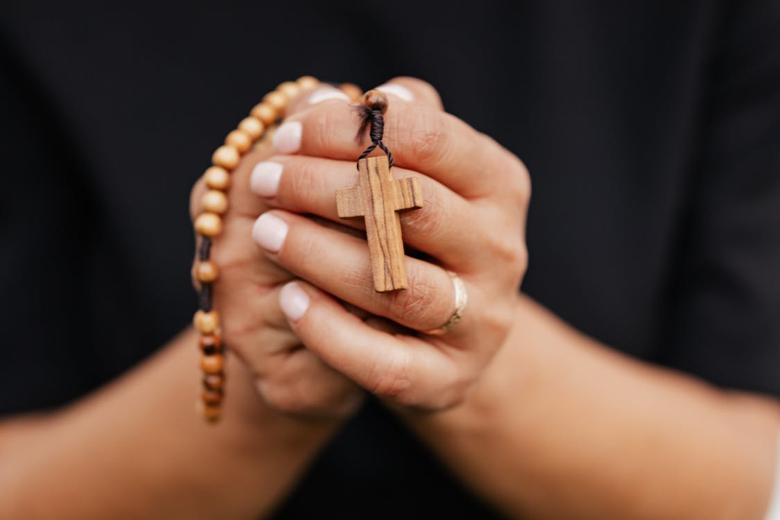 Person Holding Brown Wooden Cross Pendant