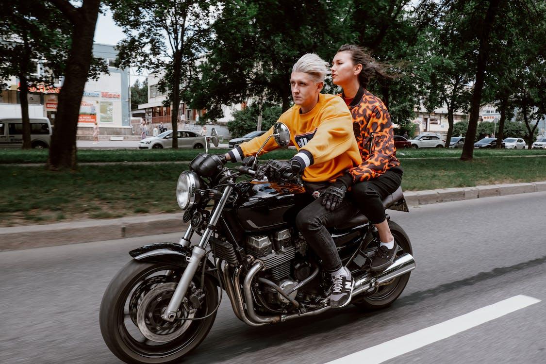 Man in Orange Jacket Riding Black Motorcycle