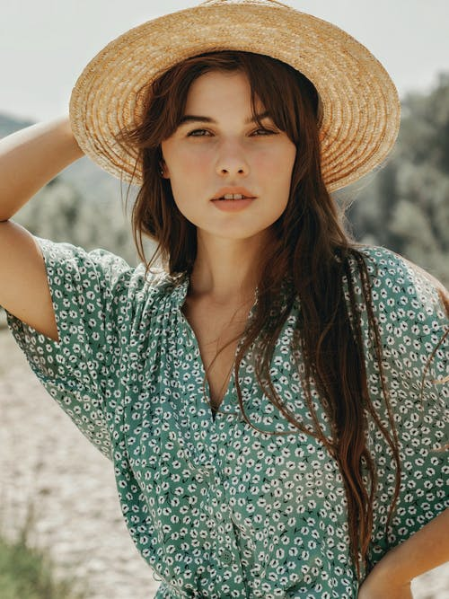 Calm woman in straw hat and summer dress
