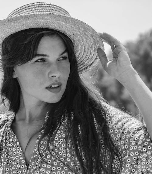 Woman touching straw hat while enjoying summer
