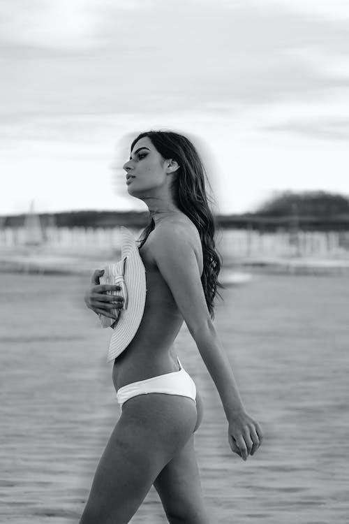Sexy woman in bikini covering naked breast