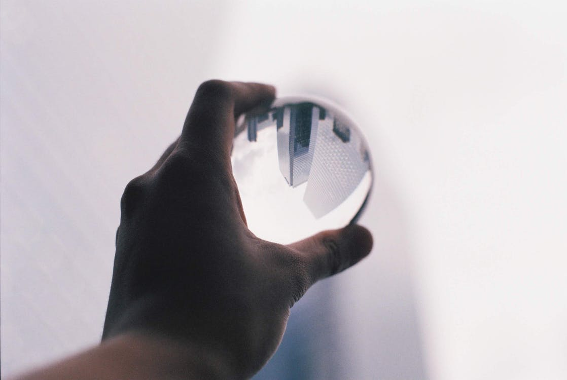 Crop anonymous person demonstrating transparent glass ball in hand against white wall with upside down reflection of modern tall skyscrapers in daylight