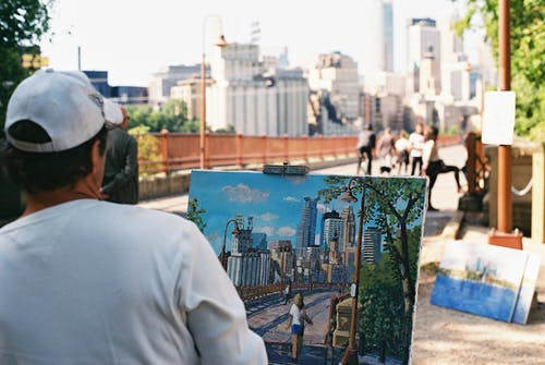 Back view of anonymous male artist in white cap sitting in street with painted picture from nature on easel near footbridge with buildings on blurred background