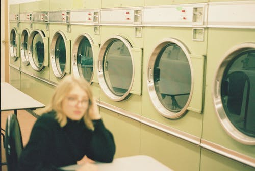 Blurred anonymous woman sitting in laundry